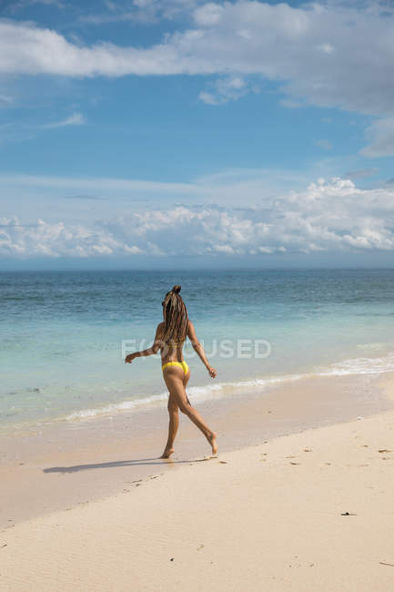 Woman in bikini walking on beach — Stock Photo