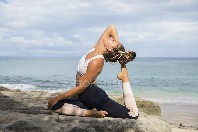 Woman stretching and posing at seaside — Stock Photo