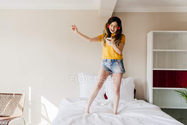 Girl dancing on bed with smartphone — Stock Photo