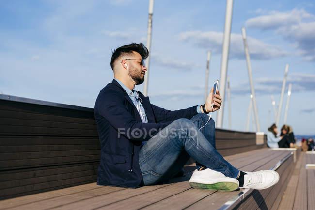 Человек расслабляющий набережную со смартфоном — стоковое фото