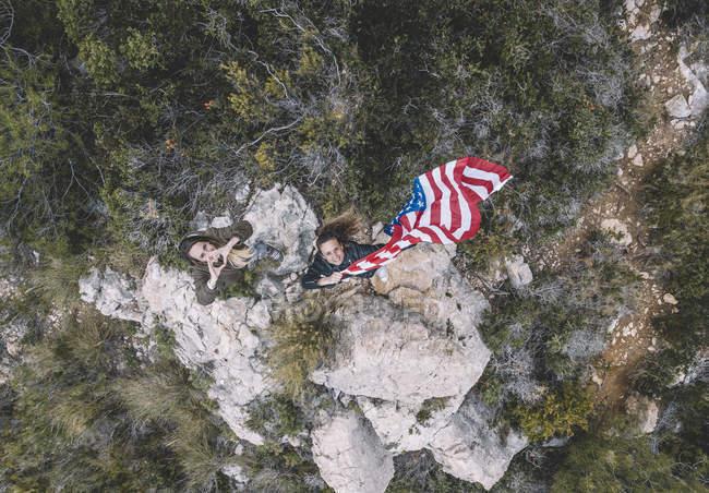 Due giovani donne in posa con bandiera USA sulle rocce . — Foto stock