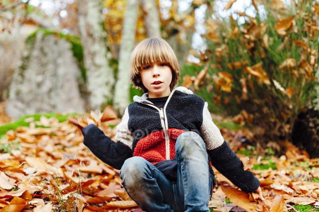 Jungen spielen mit trockenen Blätter im Wald — Stockfoto