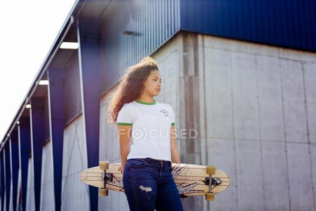 Teenage girl standing with skateboard — Stock Photo