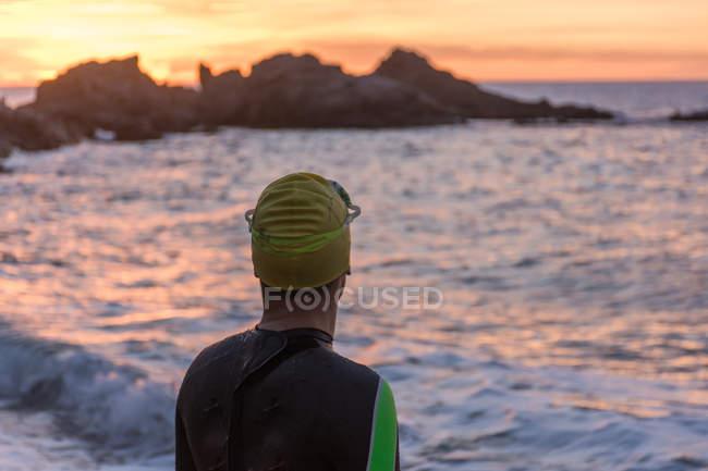 Triathlete standing on beach — Stock Photo