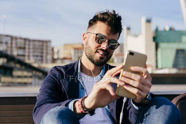 Homem relaxante com smartphone em frente ao mar — Fotografia de Stock