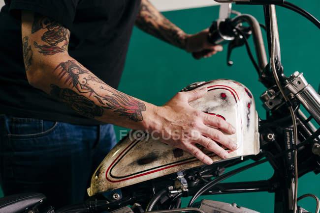 Чоловік тримає штовхає мотоцикл — стокове фото