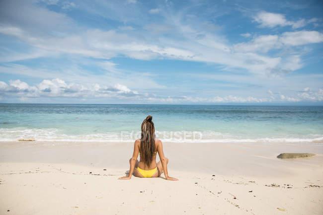 Женщина в бикини, размышляя на пляже — стоковое фото
