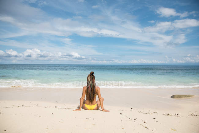 Woman in bikini meditating on beach — Stock Photo