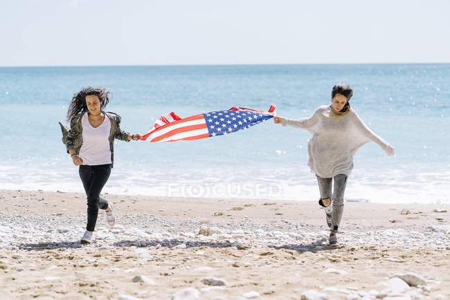 Two young adult women running on beach with USA flag. — Stock Photo