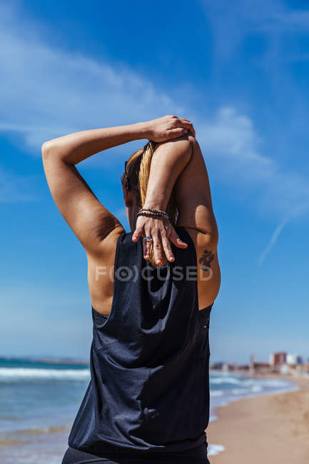 Woman exercising on beach with blue sky on background — Stock Photo