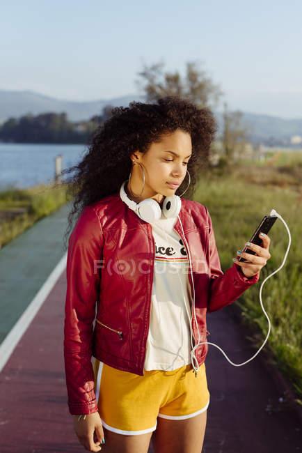 Дівчинка-підліток з смартфон стоїть на дорозі — стокове фото
