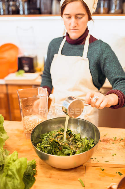 Chef pouring sauce to salad — Stock Photo