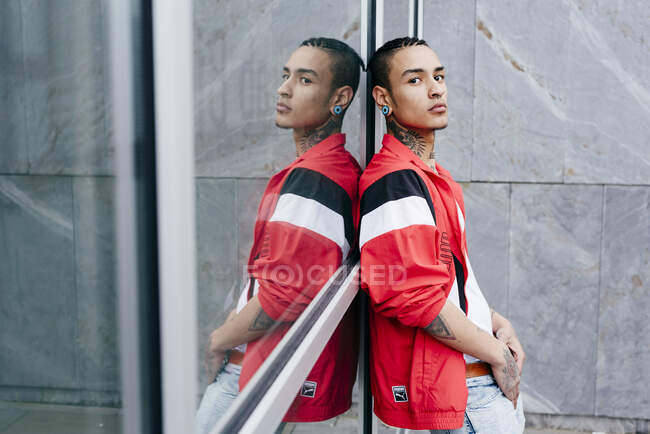 Trendy tattooed man with tunnel in ear wearing casual clothes reflecting in window looking at camera — Stock Photo