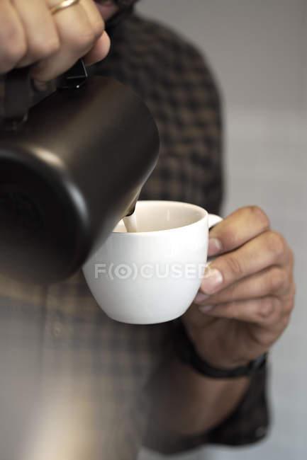 Руки баристы наливают сливки в чашку — стоковое фото