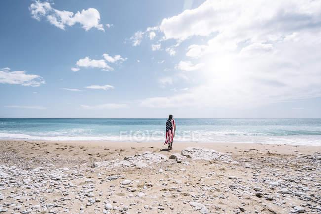Задній вид жінка постановки на пляжі, загорнуті в США прапор — стокове фото
