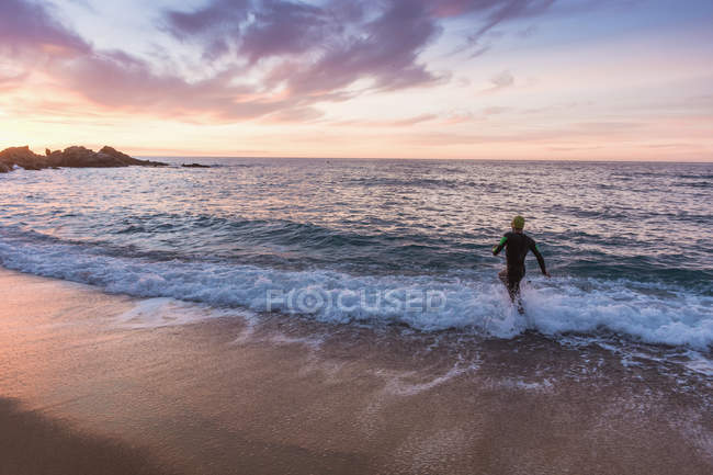 Triathlete running in wavy sea — Stock Photo