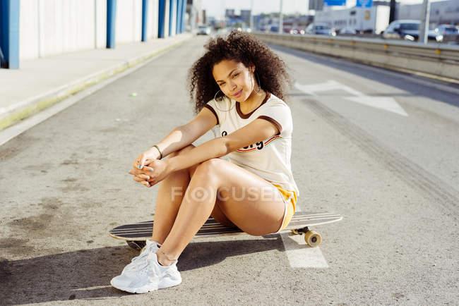 Female teenager sitting on skateboard — Stock Photo