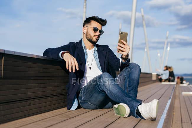 Uomo rilassante smartphone sul lungomare — Foto stock