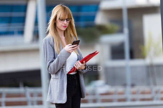 Businesswoman walking with phone and folder — Stock Photo