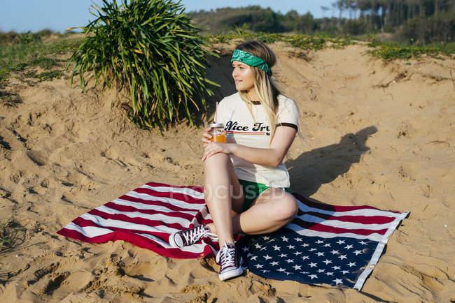 Ragazza con bevanda seduta sulla bandiera americana — Foto stock