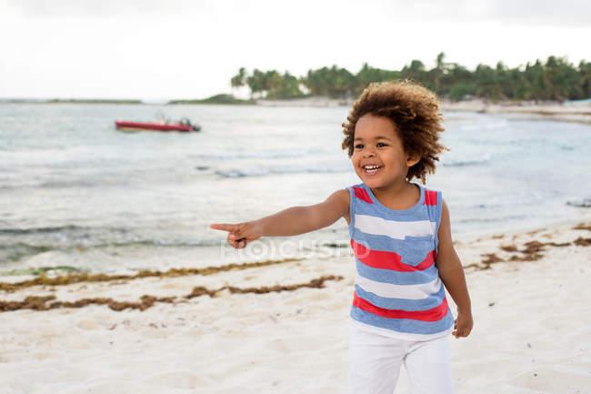 Ragazzo indicando via sulla spiaggia — Foto stock