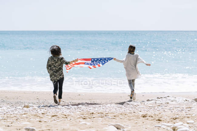 Rear view of two young women on beach with USA flag. — Stock Photo