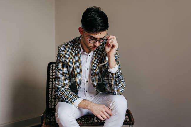 Elegante jovem sentado na cadeira — Fotografia de Stock