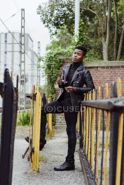Uomo nero appoggiato sulla recinzione — Foto stock