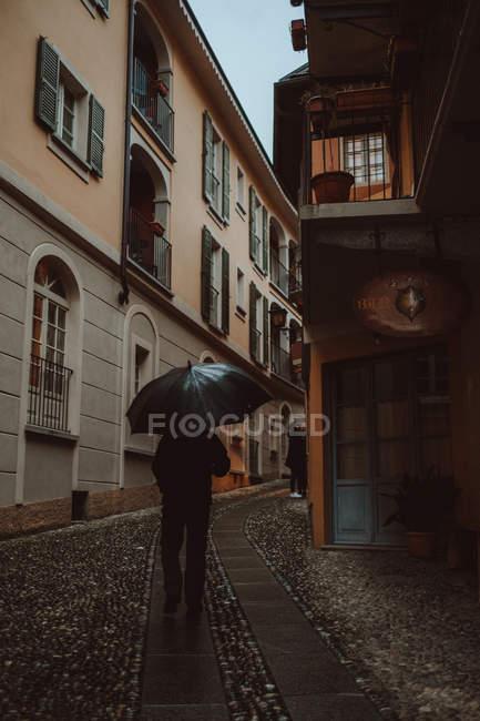 Homem andando com guarda-chuva na rua da cidade — Fotografia de Stock