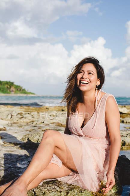 Сміється жінка, сидячи на узбережжі — стокове фото