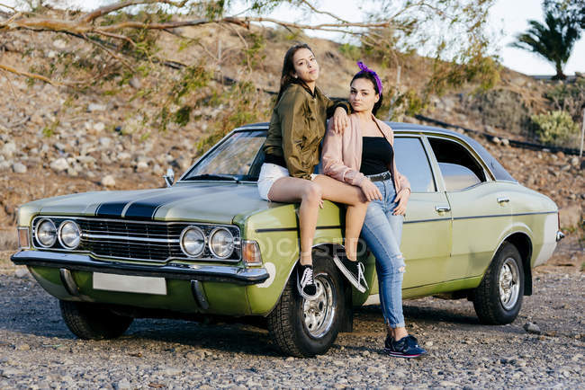 Women posing at vintage green car — Stock Photo