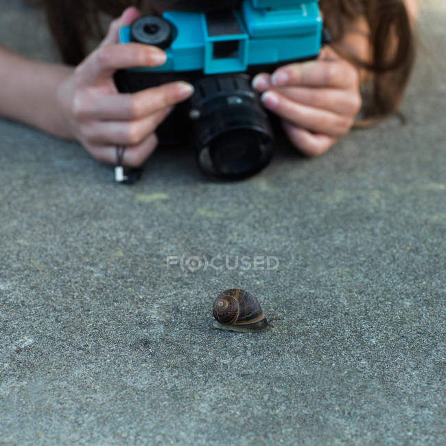Female hands shooting snail — Stock Photo