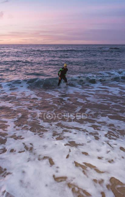 Triathlete standing in sea surf — Stock Photo