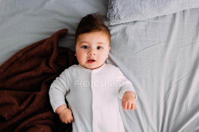 Любопытный мальчик, лежащий на кровати — стоковое фото