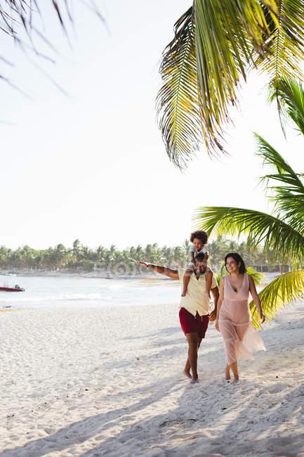 Família feliz andando na praia — Fotografia de Stock