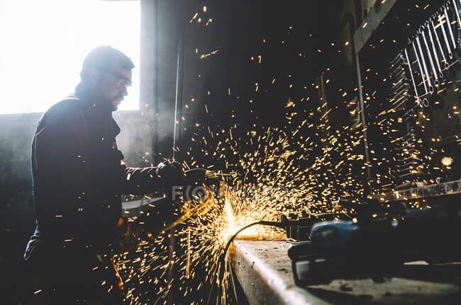 Homem trabalha com moedor de corte de metal. — Fotografia de Stock