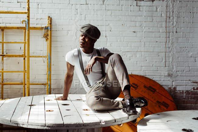 Черный человек, сидя на деревянный стол — стоковое фото