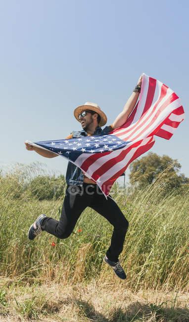 Человек прыгает с американским флагом — стоковое фото
