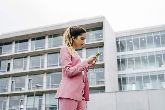Женщина в розовом костюме с помощью смартфона — стоковое фото