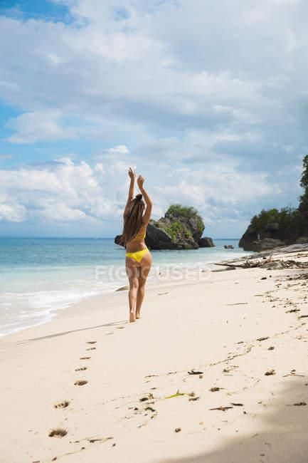 Donna in bikini camminando sulla spiaggia — Foto stock