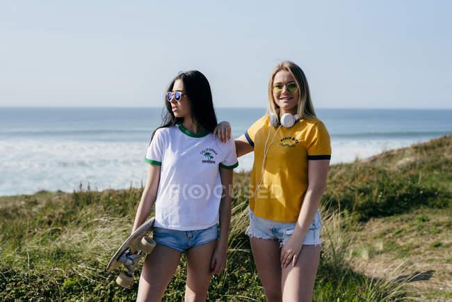 Teenage girls with longboard standing on coast — Stock Photo