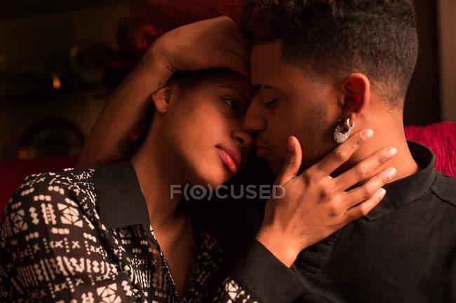 Paar auf Couch umarmt — Stockfoto