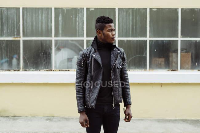 Nero uomo in piedi contro edificio — Foto stock
