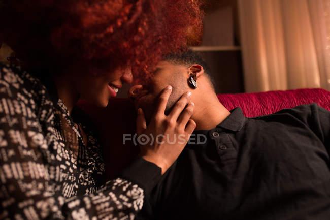 Coppia che abbraccia e bacia sul divano — Foto stock