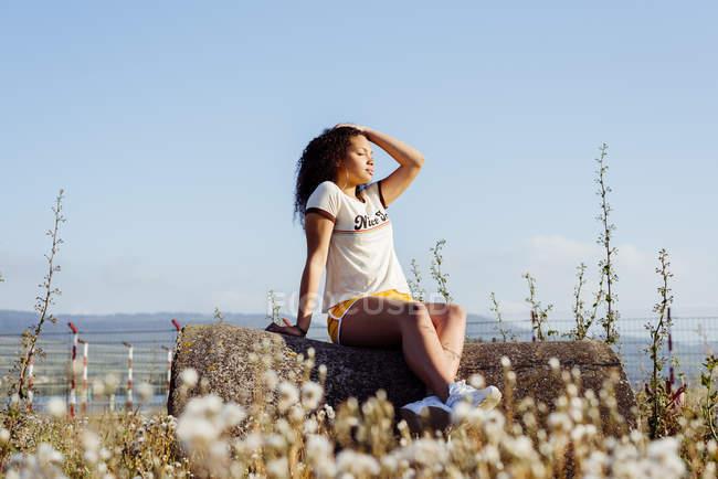 Teenage girl relaxing on log on coast — Stock Photo