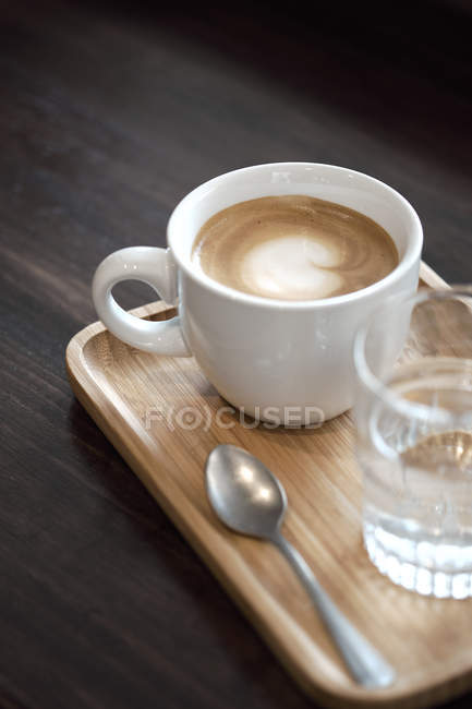 Cup of cappuccino and glass of water — Stock Photo