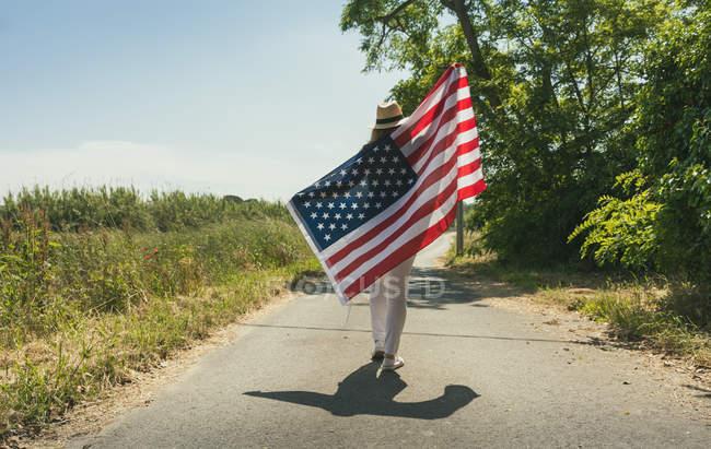 Frau läuft mit amerikanischer Flagge — Stockfoto
