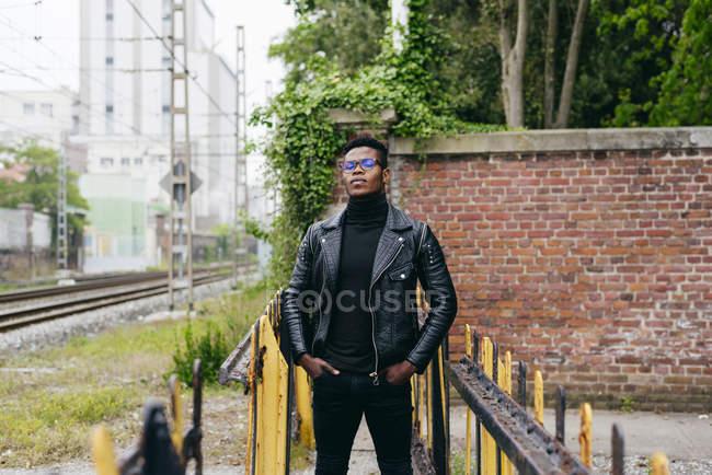 Nero uomo in piedi a ringhiera — Foto stock