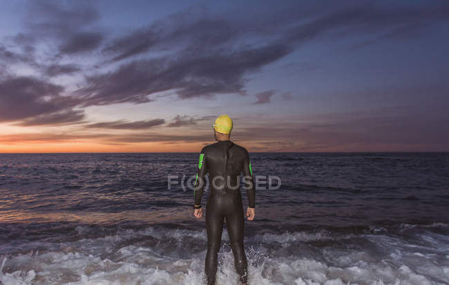 Triathlete standing at sea — Stock Photo