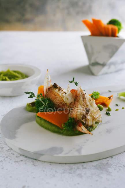 Gegrillte Drachenkopf mit Erbsenpüree und Karotten-Sticks auf Marmorplatte — Stockfoto